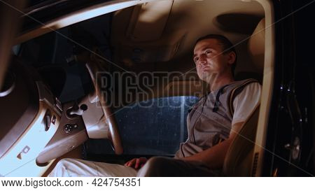 Close Up Of Young Man Sitting In Car Behind Wheel And Looking Away In Nighttime. Tired Guy Resting I