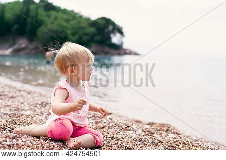 Little Girl Sits On A Pebble Beach Near The Water Against The Backdrop Of A Green Island