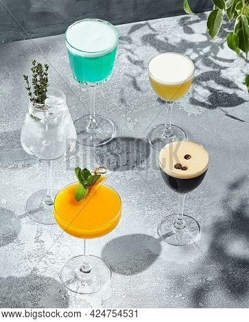 Cocktail set on vintage table with sunshine and long shadow. Different alcohol cocktail collection on textured background. Palm leaf shadow. Cocktail summer party concept