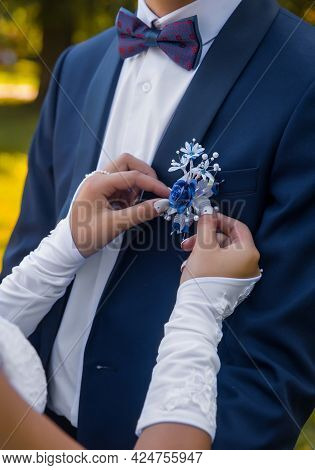 Wedding. Hands Of The Bride In Wedding Gloves Adjust The Decoration In The Form Of A Rose Flower On