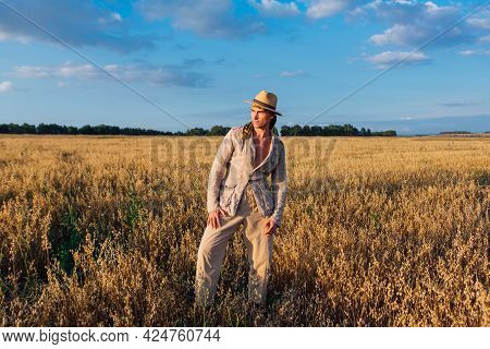 Tall Handsome Man Dressed In A Coarse Linen Suit And Hat Standing At Golden Oat Field