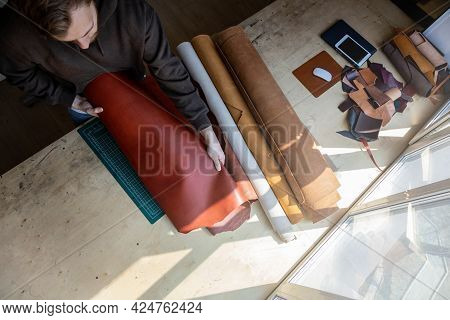 Craftsman Unwrapping Bundle Of Stuff Natural Material Working At Leather Workshop. Leatherwork