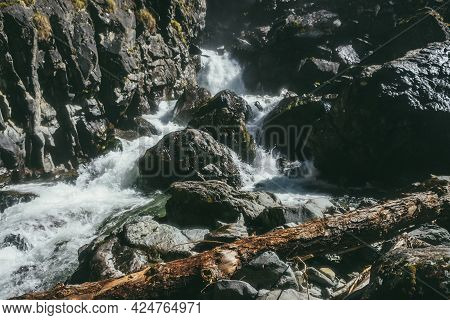 Dark Atmospheric Mountain Landscape With Turbulent Mountain River Among Black Rocks With Moss In Nar