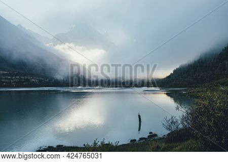 Atmospheric Alpine Landscape With Mountain Lake And High Snow-covered Mountain In Dense Low Clouds.