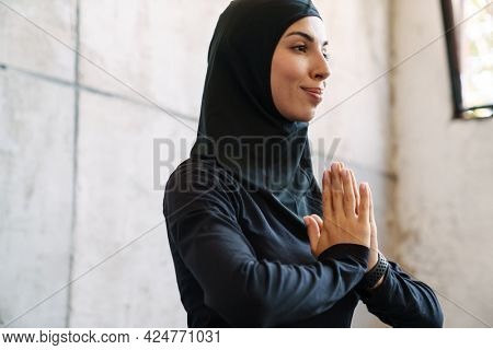 Young muslim woman in hijab meditating while sitting indoors