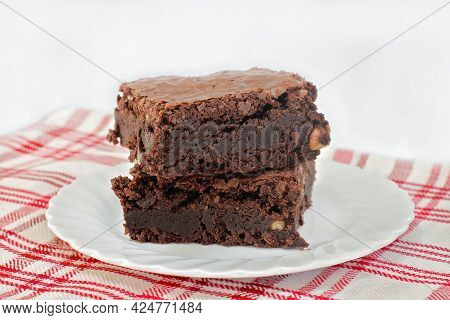 Two Stacked Chocolate Fudge Walnut Brownies On A Plate.  Shallow Focus And Copy Space.