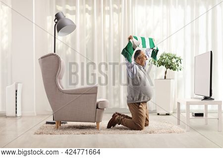 Excited mature man kneeling in front of a tv and cheering with a scarf in a living room