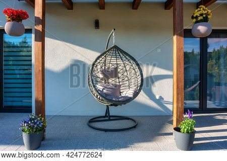 Modern hanging rattan chair with gray pillow and flowers on the summer garden terrace