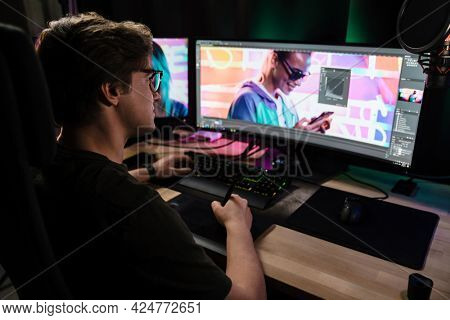 Back view of a young white man videographer working on a project with a touchpad on computer sitting at the desk indoors