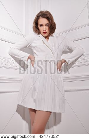 Fashion shot. Glamorous young woman with evening makeup poses in elegant white dress in classis white interior.