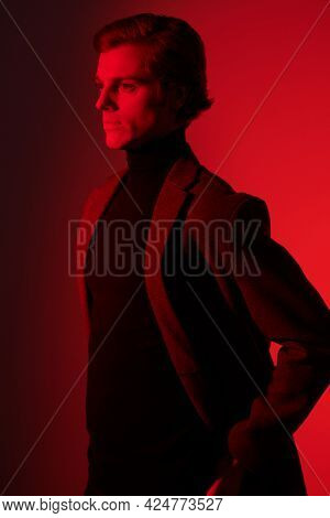 Portrait of a serious handsome man in elegant clothes posing at studio in red light. Men's beauty. Fashion.