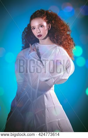 Portrait of a refined fashion model girl with lush red curly hair posing in a white haute couture dress. Art and fashion. Studio shot in mixed color light.