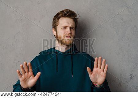 Portrait of a frowning frustrated young white casual man standing over gray background showing stop gesture with outstretched arms