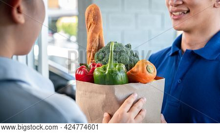 Woman Customer Standing At The House To Accepting A Grocery Bag Of Food, Fruit, Vegetable From Asian