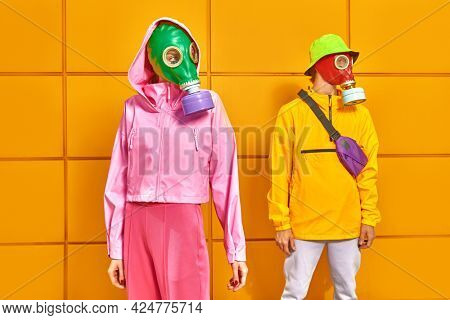 Fashion of the future. Portrait of a woman and a man in bright clothes and gas masks posing by a yellow industrial wall. Environmental disaster, apocalypse.