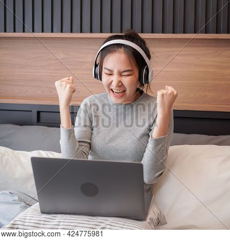 Close Up Of Young Asian Woman With Headphone Put Laptop On Pillow To Working About Business And Rais