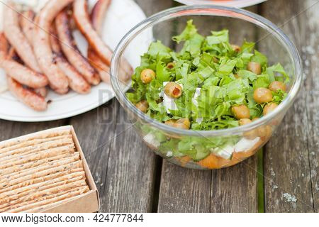 Fresh Healthy Salad With Olives And Feta Chees On Wooden Table. Baked Crisps With Sausages At The Pi