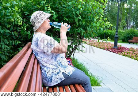 Grandma Drinks Water. An Elderly Woman Is Holding A Bottle Of Water While Sitting On A Park Bench.