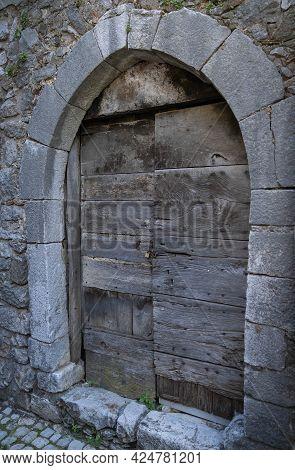 Image Of Ancient Boarded Door In A Stone Wall In Castro Del Volsci, Fronzinone, Italy