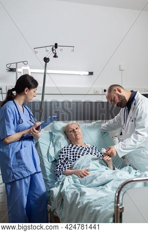 Nurse Is Taking Notes On Clipboard During Consultation Of Senior Woman, While Doctor Is Reading Data