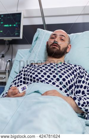 Sad Sick Man With Nasal Oxygen Tube Resting In Bad Looking Into Camera During Respiratory Recovering