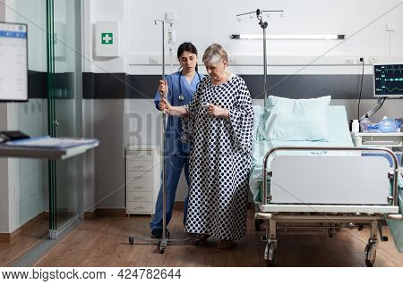 Mature Old Sick Woman Getting Intravenous Medicine From Iv Drip Bag. Medical Nurse Helping Patient W