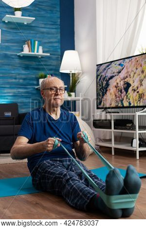 Focused Pensioner Sitting On Yoga Mat Stretching Legs Muscle Using Fitness Elastic Band During Aerob