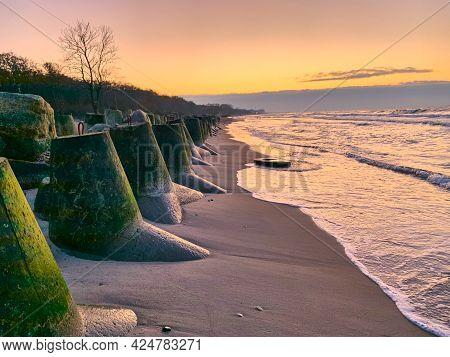 Breakwaters With Algae Seascape At Sunset. Seashore And Sunrise Breakwater Concrete Tetrapods, Wave