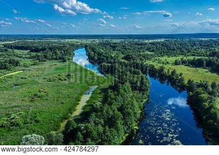 Beautiful panoramic view of river and green banks of the river in the summer morning day. Aerial panoramic view.