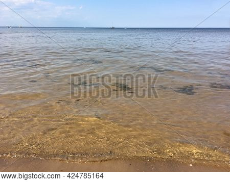Europe, Latvia, Jurmala. The Shore Of The Gulf Of Riga During The Calm With A Yacht Near The Horizon