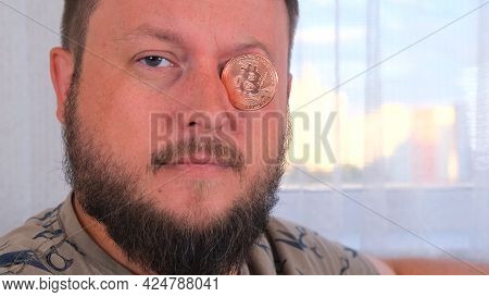 Man Holds Bitcoins. Male With Bitcoin In Eye. Bitcoin Is A Cryptocurrency Invented In 2008 By An Unk