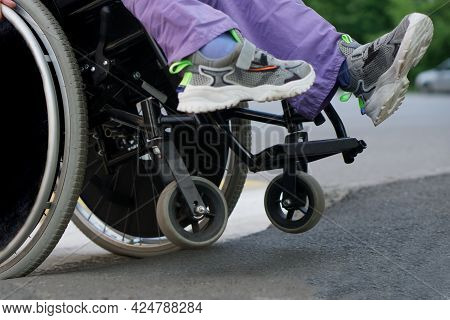 A Paralyzed Girl In A Wheelchair Drives A Dangerous Curb On Two Wheels. Risk Of Accident And Crash.