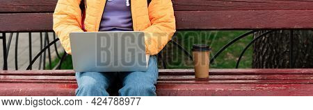 Cropped View Of Teleworker Using Laptop Near Coffee On Bench Outdoors, Banner