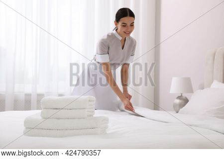 Chambermaid Making Bed In Hotel Room, Focus On Fresh Towels. Space For Text