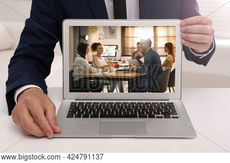 Businessman Attending Online Video Conference Via Modern Laptop At Table In Office, Closeup