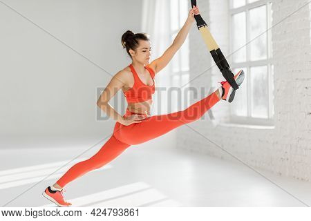 Athletic Woman Stretching With Suspension Straps, Doing Total Resistance Exercise Indoors