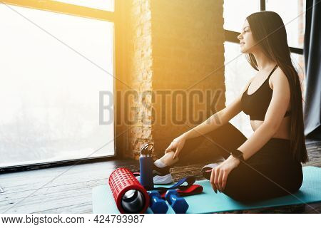 Fitness Instructor Is Sitting On The Floor. Sports Equipment, Dumbbells, Elastic Band, Fascia Roll L