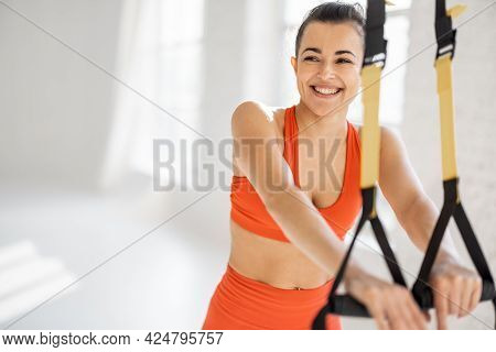 Portrait Of A Cheerful Athletic Woman Training On Suspension Straps At White Sunny Gym. Trx Training