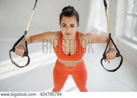 Athletic Woman In Bright Sportswear Doing Push Ups On Suspension Straps At White Gym. Trx Training O