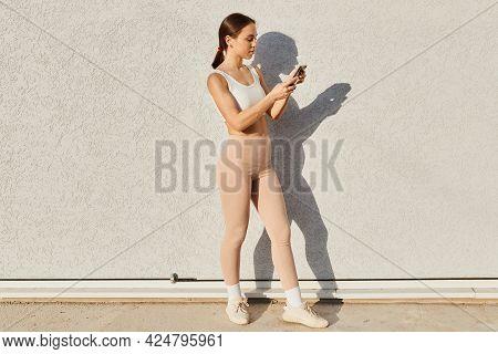 Full Length Profile Portrait Of Brunette Female Wearing White Top And Beige Leggins, Holding Smart P