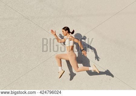 Portrait Of Woman With Perfect Body Jumping Over In The Air, Wearing White Top And Beige Leggins, Do