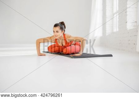 Athletic Woman Stretching In A Yoga Pose, Practising Hatha Yoga At White Room Alone