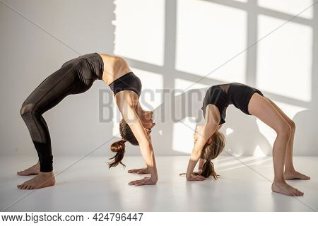 Young Mom Or Sports Trainer Doing Gymnastics With A Little Girl Indoors. Individual Lesson In Rhythm