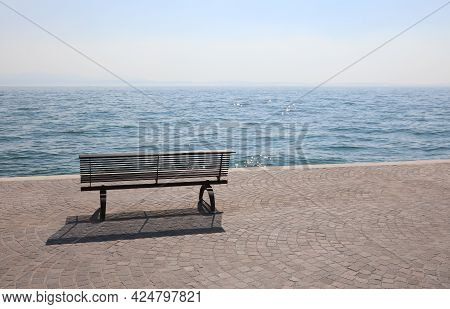 Lonely Bench On The Shore With The Placid Water Symbol Of Tranquility And Relaxation Without People
