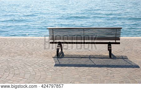 Bench On The Shore With The Placid Water Symbol Of Tranquility And Experience
