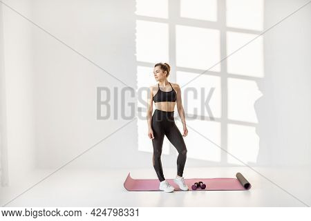 Portrait Of A Beautiful And Confident Athletic Woman Doing Cardio With Dumbbells At White Room. Trai