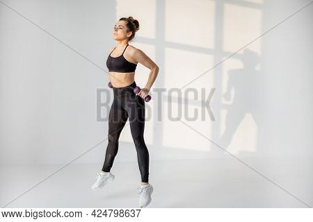 Beautiful And Confident Athletic Woman Doing Cardio With Dumbbells At White Room. Training Fitness O