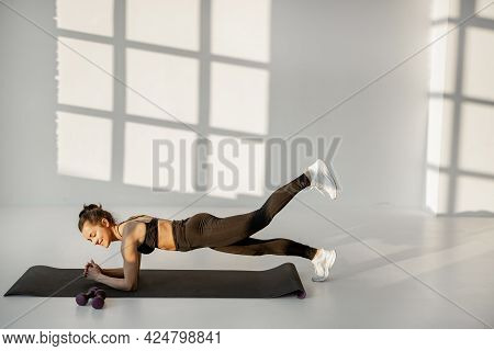 Athletic Woman Stands In The Plank On A Fitness Matt, Performing Static Exercise On A Fitness Traini