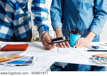 Man Carefully Studying Technical Drawing With Magnifying Glass. Designers Working With Color Swatche