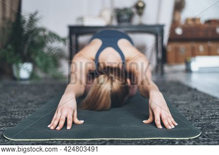 Selective Focus On Young Woman Practicing Yoga, Doing Balasana Or Child Pose Exercise. Female Workin